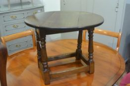 A small oak oval dropleaf swivel top occasional table, on turned baluster supports united by a
