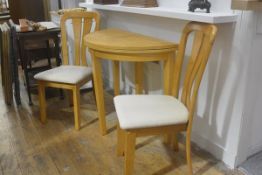 A modern three piece kitchen dining set, comprising circular foldover table raised on square