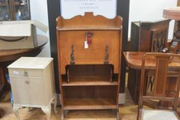 An Edwardian oak Arts & Crafts ledge back secretaire, with fall front enclosing a fitted interior,