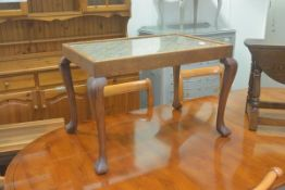 A 1920's oak glazed top rectangular coffee table, raised on tapered supports and pad feet, with