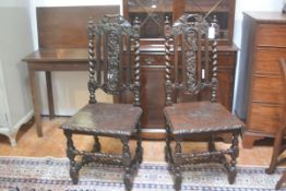 A pair of Victorian oak hall chairs, each with vine leaf and grape carved crests and splats, with