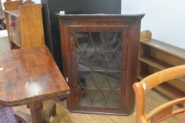 A 19th century mahogany inlaid wall hanging corner cabinet, with oval glazed door and shelved