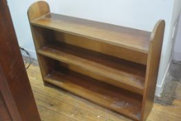 A stained teak three tier open bookcase. 73cm by 92cm by 22cm