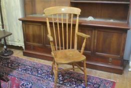 A late 19thc elm spindle back open arm kitchen chair with shaped wood seat, on ring turned splay