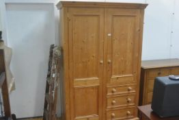 A pine gent's style wardrobe, cornice (a/f) over one long and one short panelled doors, with drawers