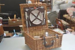 An Optima wicker picnic basket for two with leather fastening straps, complete with knife, fork,