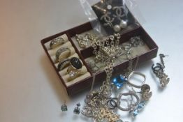 A leather jewellery case containing miscellaneous white metal and silver pendants, dress rings,