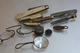 A collection of five various pocket knives, a pair of metal pince nez, a monacle, a folding tape