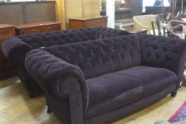 A pair of modern two seater Chesterfield button back sofas upholstered in plum plush fabric,