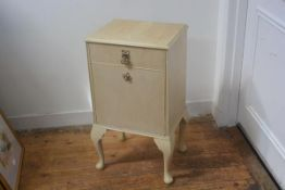 A 1930's/40's bleached walnut bedside cabinet, with single drawer over a fall front, on carved