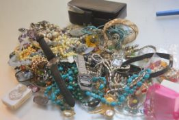 A bag containing a large collection of costume jewellery including pendants, earrings, brooches etc.