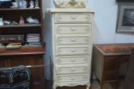 An American cream and gilt painted tallboy chest, the scalloped top with ledge back above seven long