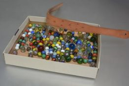 A box containing a large collection of coloured and clear glass marbles and a leather tawse (a lot)