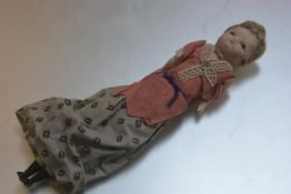 A late 19thc treen wax coated headed doll with flapper style hair in long dress, with treen