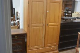 A laminated pine upright wardrobe, the plain top above a pair of fielded panel doors enclosing a