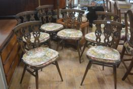 A set of six Ercol dark oak triple splat back dining chairs with shaped wood seats, raised on