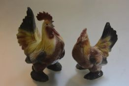 A pair of Continental china cockeral and hen figures with polychrome decoration (restorations to