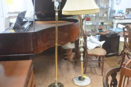 A brass circular column floor lamp raised on circular weighted base and a 1970s onyx and brass