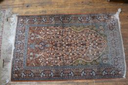 A Nepalese silk prayer rug, the centre rectangle with arched panel and hanging lantern, enclosed