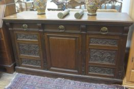 An Edwardian oak sideboard, the rectangular top with moulded edge above three frieze drawers, with