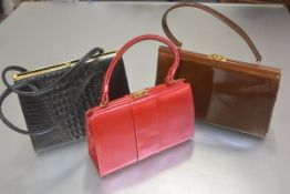 A lady's black mock crocodile skin two handled vintage handbag, a suede lined pink lustre two