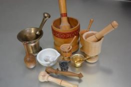 A collection of four various treen mortars and pestles, a gilt metal enamelled mortar and pestle,