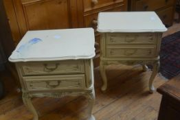 A pair of American cream finish bedsides with scalloped tops, fitted two drawers, raised on carved