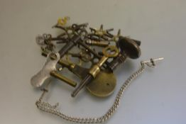 A collection of various clock and watch keys including a white metal T bar and chain (a lot)