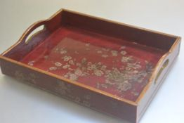 A modern red lacquered two handled rectangular tea tray with prunus and crysanthemum decoration (h.