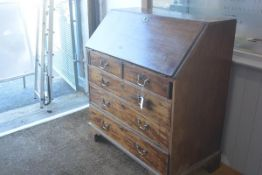 A George III mahogany bureau with fall front over two short and three long drawers, on bracket feet.