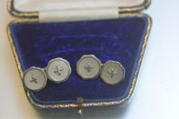 A pair of 900 standard white metal engraved mother of pearl sleevelinks with cross knot centres