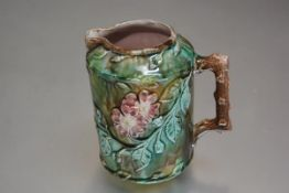 A 19thc majolica jug with moulded cherry blossom and leaf decoration with brown and green drip glaze