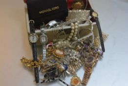 A jewellery box containing a large collection of paste jewellery including pendants, chains,