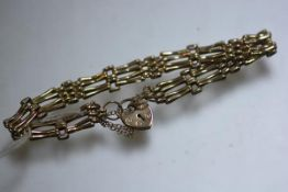 A 9ct gold gatelink bracelet complete with heart shaped padlock and safety chain (9cm) (9.68g)