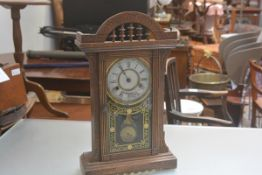 A 19thc American treen gingerbread style mantle clock with pedimented top and enamel dial, with