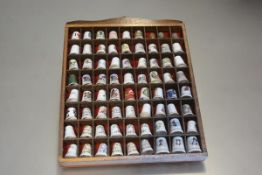 A wall display stand containing a collection of sixty nine ceramic and three metal thimbles (25cm
