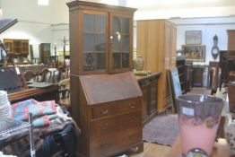An Edwardian oak two part bureau bookcase, the moulded cornice above a pair of glazed astragal