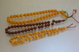 Two strands of amber coloured early bakelite worry beads and a brown strand of bakelite worry