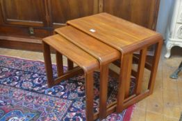 A G Plan style nest of three teak coffee tables, the rectangular tops with curved moulded edges,