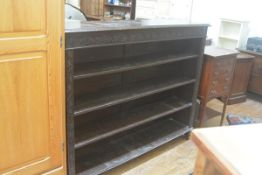 A Victorian oak upright open bookcase with relief carved arched frieze above three adjustable