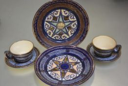 A pair of Quimper pottery coffee cups and saucers and two side plates decorated with outline lozenge