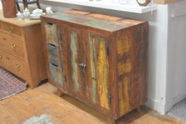 An Indian hardwood distressed finish side cabinet, fitted with a pair of panel doors flanked by