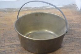 A large brass preserve pan with loop handle to top (h.10cm. d.45cm)
