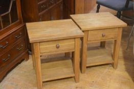 A pair of oak bedsides with square tops fitted open shelves and undershelf, on square moulded