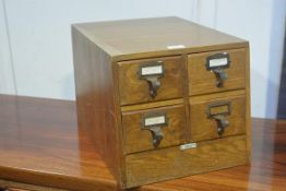 A 1920s oak four drawer index box by Libraco, London, with ivorine panel to slope front (h.29cm x