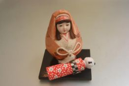 A Japanese Kokeshi style doll and a baby doll complete with hardwood stand (h.18cm and 16cm) (2)
