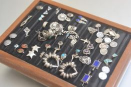 A showcase containing a collection of silver and white metal rings, earrings, bracelets, some with