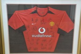 A Manchester United red and black shirt, signed by the complete team including David Beckham, c.