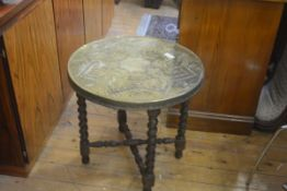 An Eastern brass circular top coffee table with lion mask centre panel enclosed within a foliate and