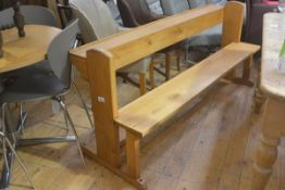 An oak church pew with shelf back, on shaped arched top side supports with plank seat (h.76cm x
